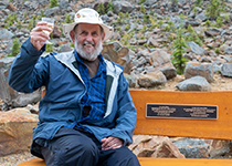 Brian Luckman sittin on bench dedicated to him by Parks Canada in the Canadian Rockies